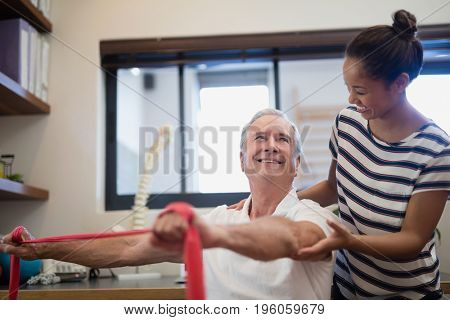 Smiling senior male patient pulling red resistance band while looking at female doctor in hospital ward