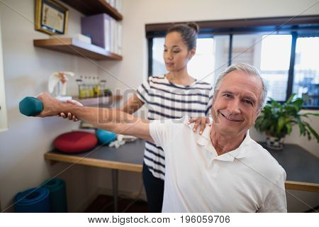Female doctor holding hand of smiling senior male patient lifting dumbbell at hospital ward