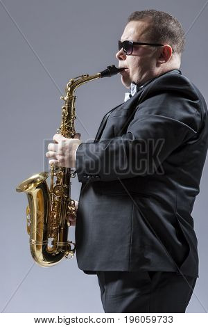 Music Ideas and Concepts. Portrait of Mature Caucasian Saxophone Player in Sunglasses Playing the Saxophone in Studio Environment. Vertical Image