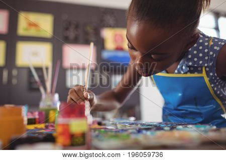 Concentrated elementary girl painting at desk in classroom