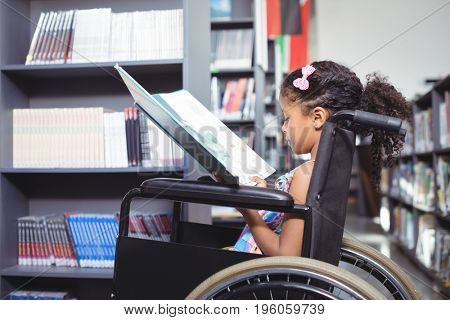 Side view of girl reading book while sitting on wheelchair in library