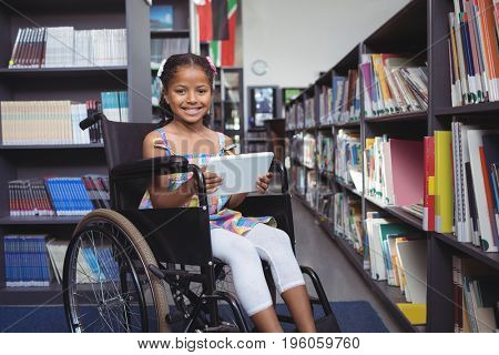 Portrait of girl on wheelchair smiling while holding digital tablet in library