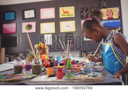 Side view of girl holding brush by color palettes on desk in classroom