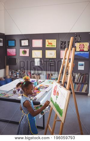 High angle side view of girl painting on canvas in classroom