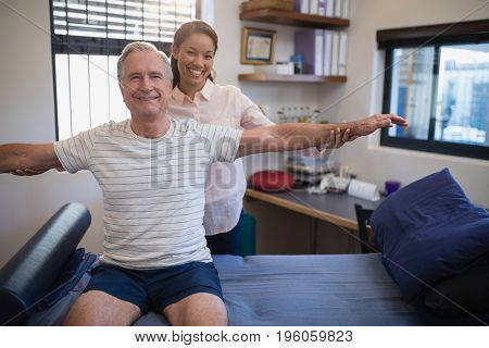 Smiling female doctor and male patient with arms outstretched at hospital ward