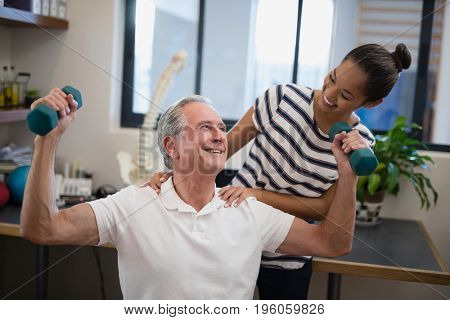 Smiling female doctor looking at senior male patient lifting dumbbells in hospital ward