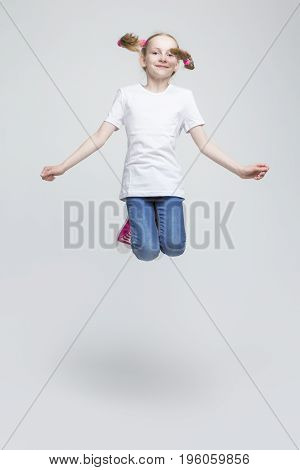 Portrait of Happy Smiling Caucasian Blond Girl With Pigtails Making a High Jump in Studio. Against White Background. Vertical Shot