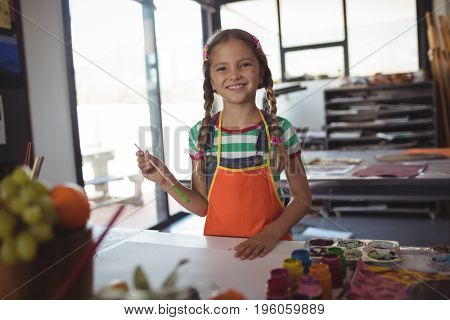 Portrait of smiling girl standing at painting class