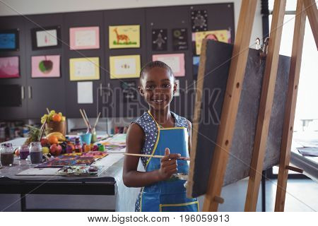 Portrait of smiling girl painting on canvas in classroom