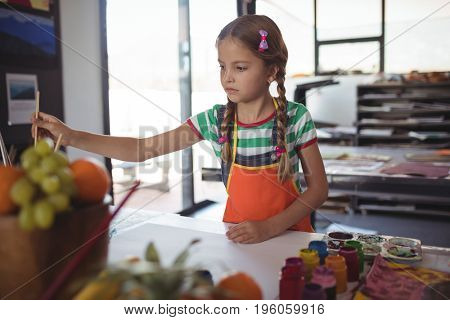 Girl painting at desk in classroom at school