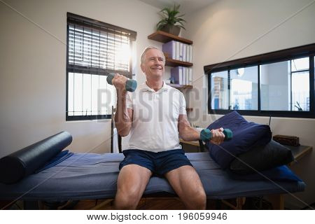 Smiling senior male patient lifting dumbbells while sitting on bed at hospital ward