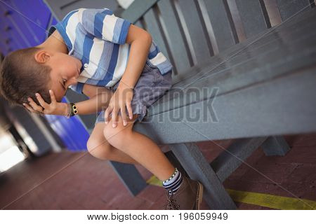 Sad boy with head in hand sitting on bench at school corridor