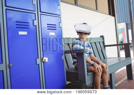 Boy using virtual reality glasses while sitting on bench by lockers in corridor at school