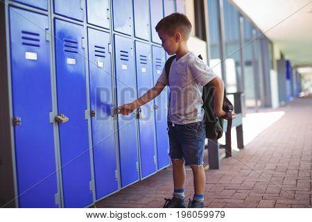 Boy locking locker while wearing bag in corridor at school