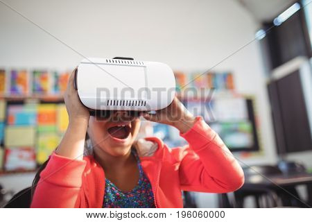 Cheerful girl using virtual reality glasses in classroom at school