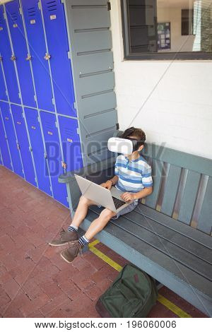Boy using laptop and virtual reality glasses while sitting on bench by lockers at school