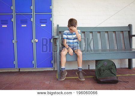Full length of sad boy sitting on bench by lockers at school