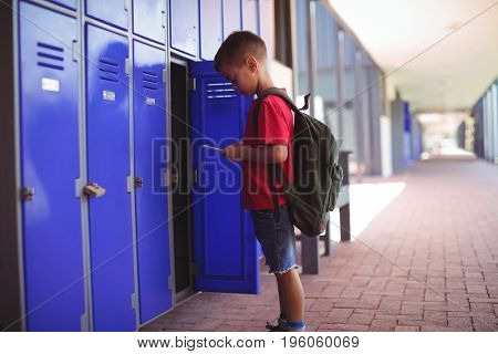 Boy using mobile phone by open locker in corridor at school