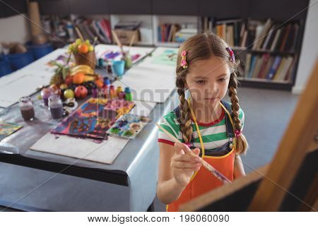 High angle view of girl painting on canvas in classroom