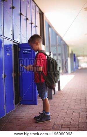 Side view of boy using mobile phone by open locker in corridor at school