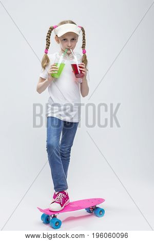 Kids Concepts. Portrait of Little Caucasian Blond Girl in Visor Posing on Pennyboard With Two Cups of Juice and Straw. Against White. Vertical Image Composition