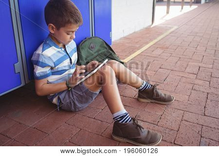 Boy using digital tablet while sitting by locker in corridor at school