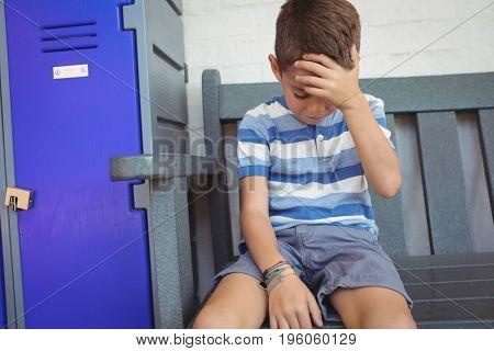 Sad boy sitting on bench by locker at school