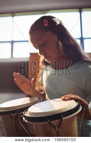Girl practicing bongo drums in classroom at music school