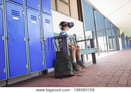 Full length of boy using virtual reality glasses while sitting on bench by lockers in corridor at school