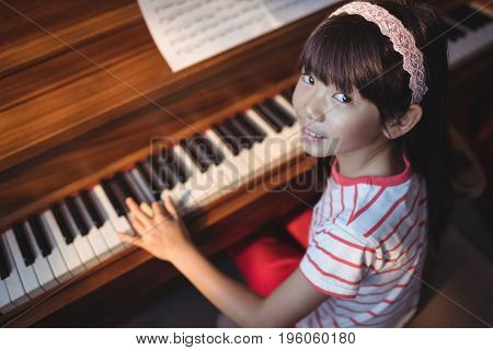 High angle portrait of girl practicing piano in classroom at music school
