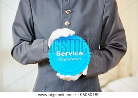 Hotel page holding badge with service guarantee in his hands