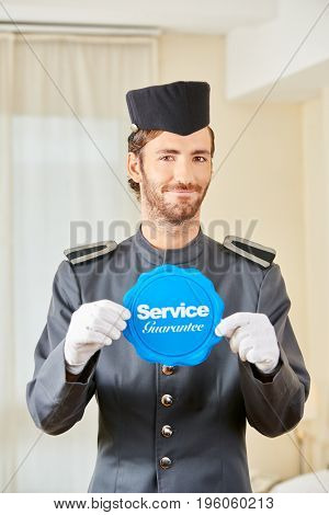 Hotel page holding service guarantee badge in hotel room