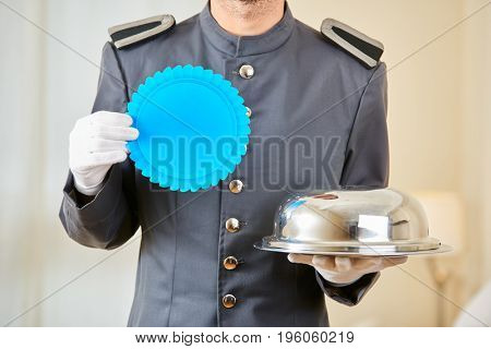 Page in hotel with food cloche and blank blue badge in his hands