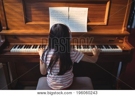 Rear view of girl practicing piano in classroom at music school