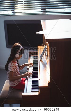High angle side view of girl wearing headphones while practicing piano in classroom at music school