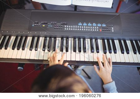 Cropped image of girl playing piano in class at school