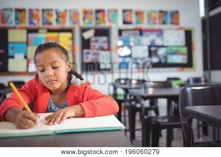 Girl studying while sitting at desk in classroom