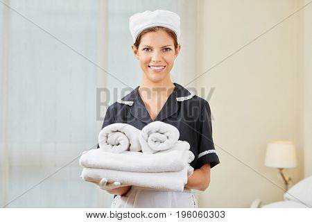 Maid in uniform during housekeeping in a hotel room holding fresh clean towels