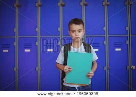 Portrait of boy holding books while standing against lockers at school