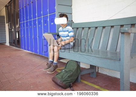 Full length of boy using laptop and virtual reality glasses while sitting on bench by lockers in corridor at school