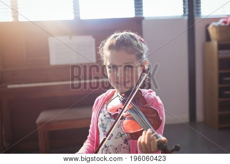 Portrait of smiling girl student rehearsing violin in music class