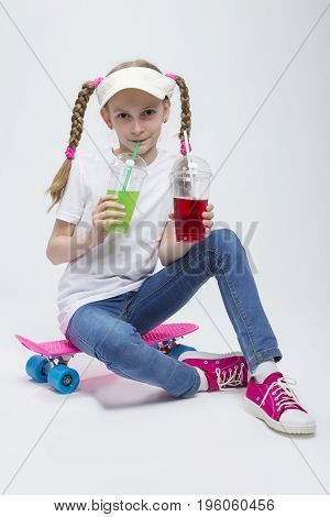 Kids Concepts. Portrait of Little Caucasian Blond Girl in Visor Sitting on Pink Pennyboard With Two Cups of Juice and Drinking Through Straw. Against White. Vertical Image