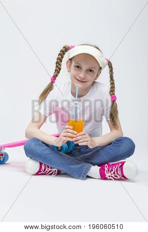 Kid Ideas and Concepts. Portrait of Smiling Happy Caucasian Blond Girl wearing Visor Sitting on Floor with Cup of Juice and Drinking Through Straw. Vertical Image