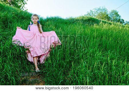 Happy little girl in beautiful long dress in a summer park. Children's fashion. Happy summer holidays.