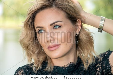 Beautiful middle aged woman having a rest at a park on a summer day. Mood of summer and carefree vacations. Beauty, cosmetics.