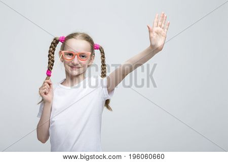 Kids Concepts. Portrait of Positive Caucasian Blond Girl With Pigtails Posing with Artistic Spectacles Against White Background. Horizontal Image Orientation