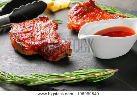 Delicious pork ribs with tomato sauce and rosemary on table, closeup
