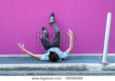 Young man fall on grill. Fuchsia background