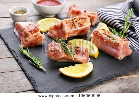 Slate plate with raw pork ribs and lemon slices on wooden table