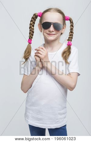 Kids Concepts. Portrait of Positive Caucasian Blond Girl With Pigtails Posing with Artistic Spectacles Against White Background. Vertical Image